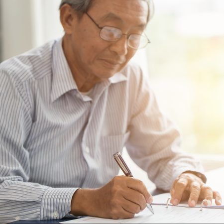 senior Asian man signing paper