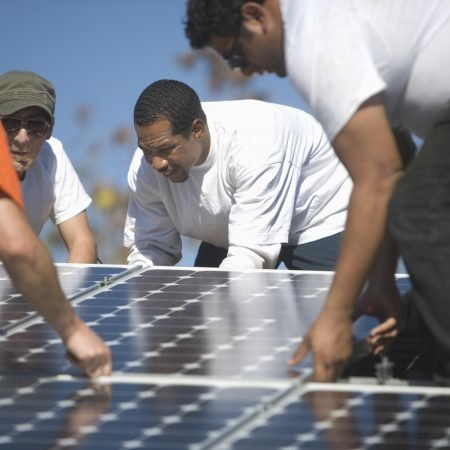 Group of multiethnic engineers placing solar panel on rooftop