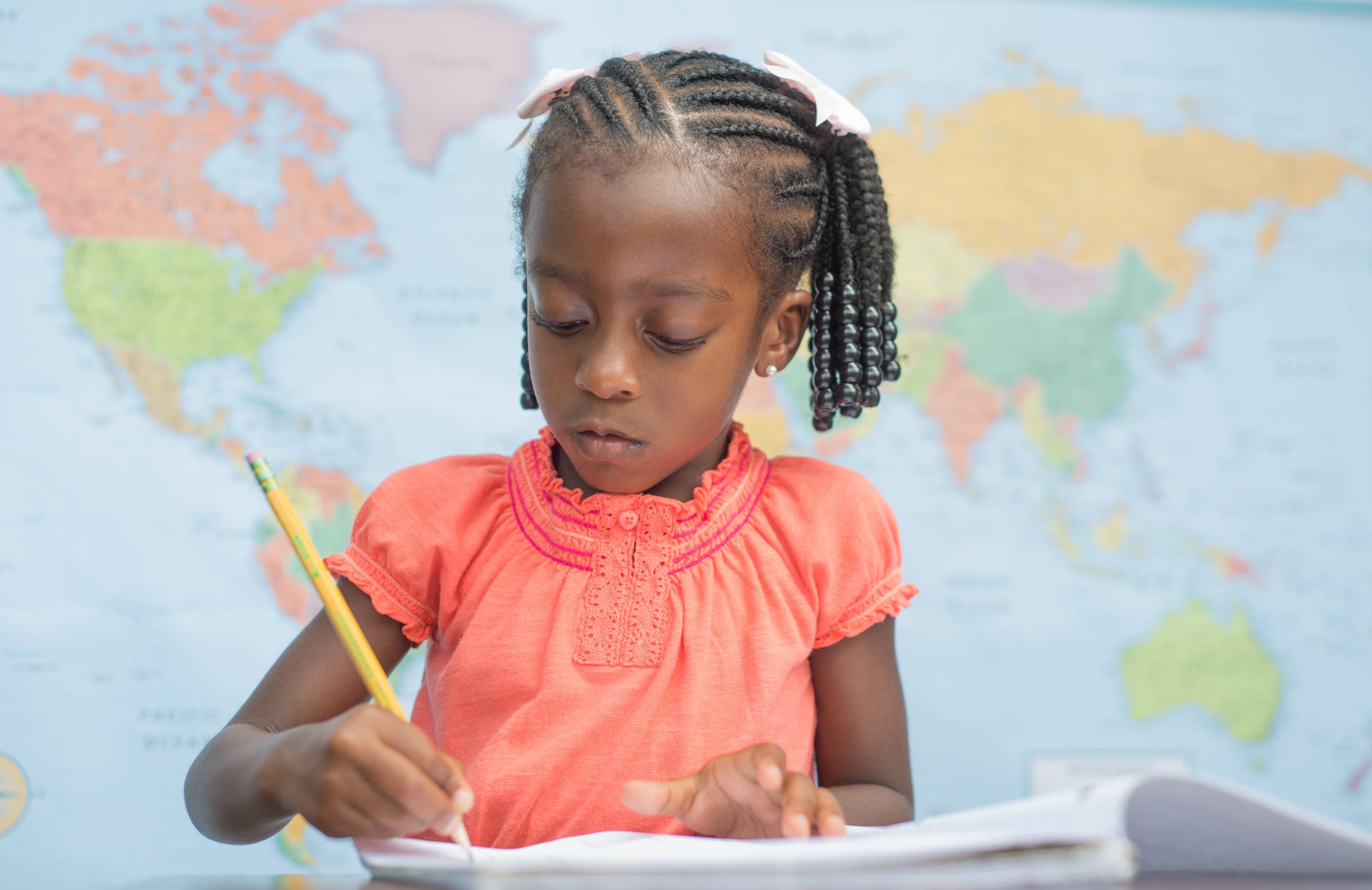 young preschool girl writing in notebook