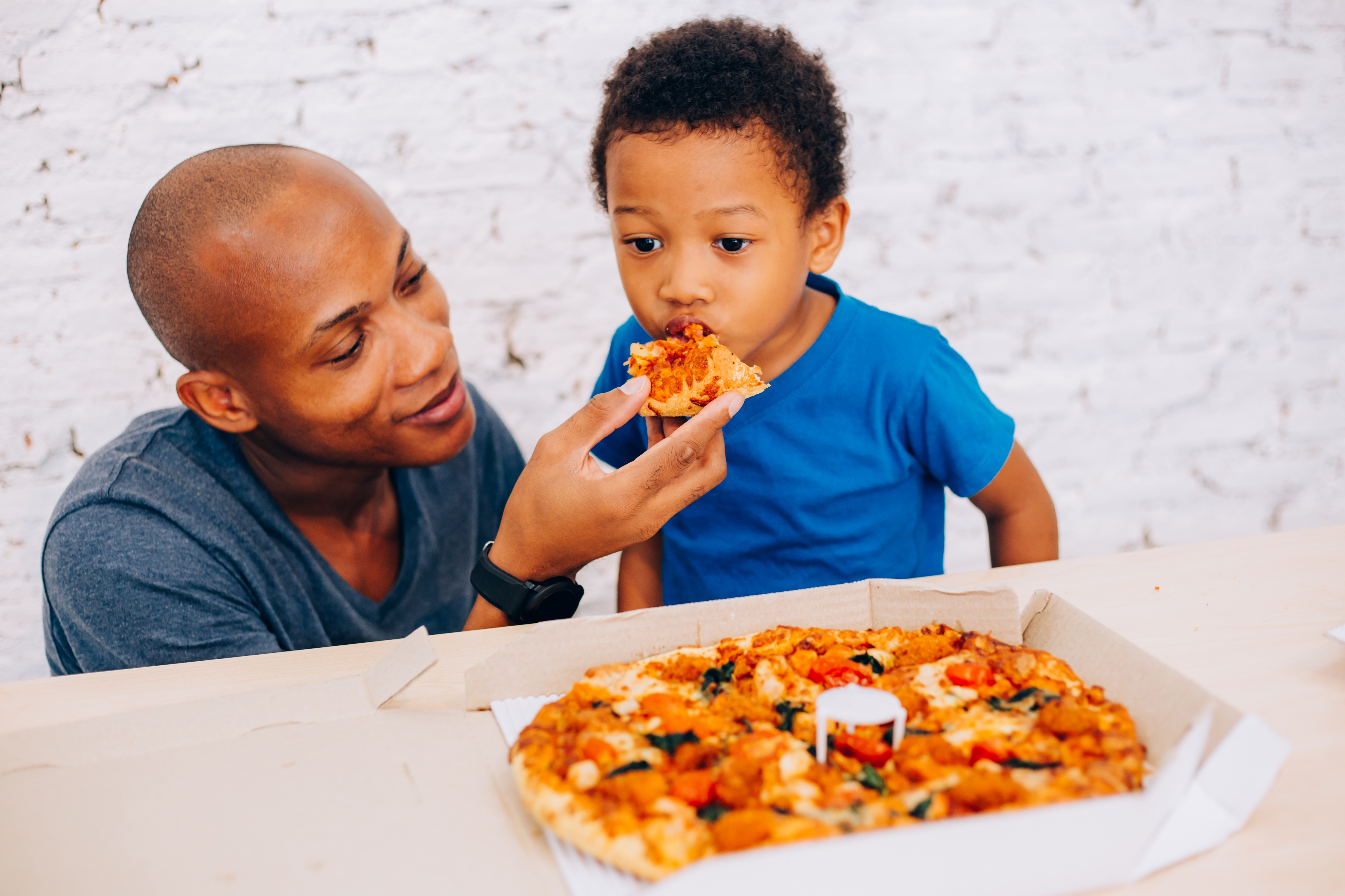 father feeding pizza to son