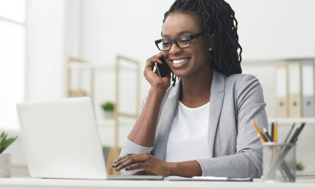 Happy Business Woman Having Phone Conversation Using Laptop In Office